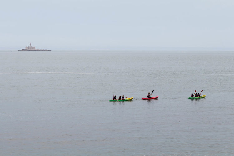 Distant View Of People Canoeing On Sea Against Sky