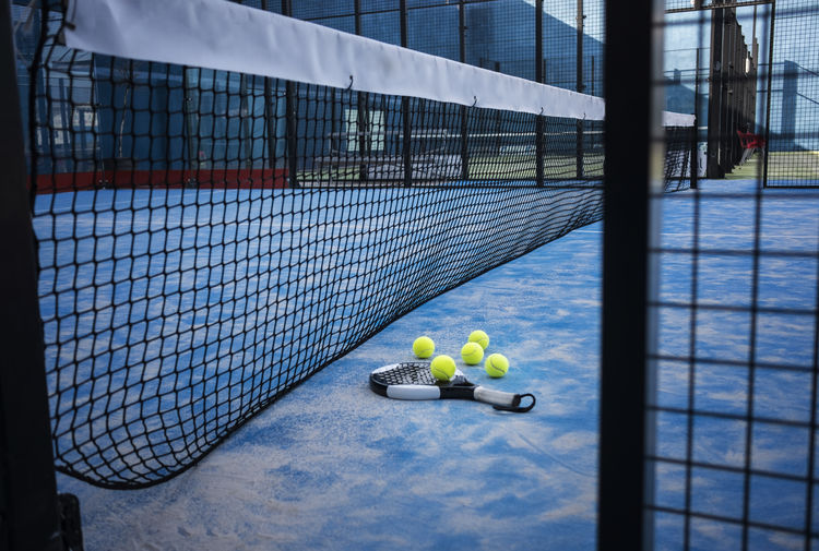 """Paddle tennis racket and balls on court artificial grass. """"PADDLE TENNIS"""" KEY WORD Paddle Tennis Padel Paddle Tennis Court Sport Recreation  Racket Racquet Balls Blue Concrete Artificial Grass Outdoors Indoor Sport Recreation  Nobody Net Equipment Fence Paddle-tennis Still Life Game Play Match"""