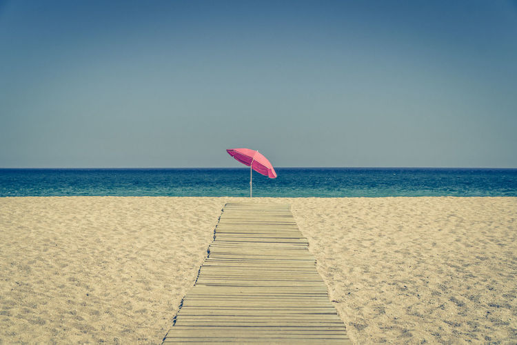 Sun umbrella standing alone at the end of a wooden pavement on an empty sandy beach with crystal clear sea waters in background Beach Beauty In Nature Blue Clear Sky Day Horizon Horizon Over Water Nature No People Outdoors Sand Scenics Sea Sky Summer Tranquil Scene Tranquility Vacations Water Weekend Activities Sommergefühle