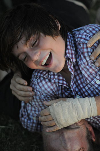 Close-up of cheerful teenager with injured hand falling on father at field