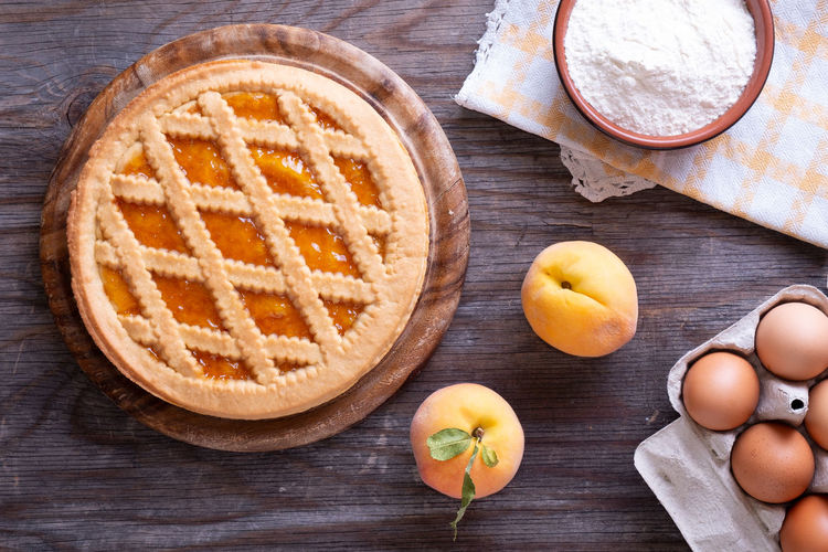 Tart with peach jam on wooden rustic table Tart Bowl Dairy Product Directly Above Drink Food Food And Drink Freshness Fruit Glass Healthy Eating High Angle View Household Equipment Indoors  Ingredient Kitchen Utensil No People Peaches Pie Preparation  Refreshment Still Life Table Table Knife Wood - Material