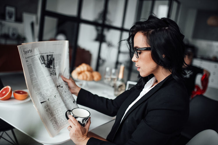 Woman holding drink while sitting at cafe