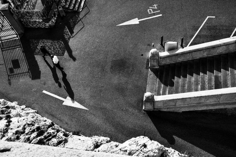 High Angle View Of Men Walking On Street By Steps