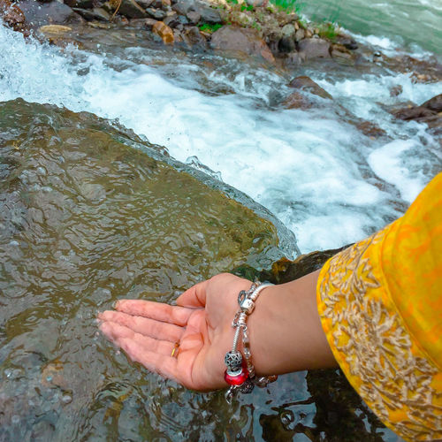 Cropped hand touching flower water in river