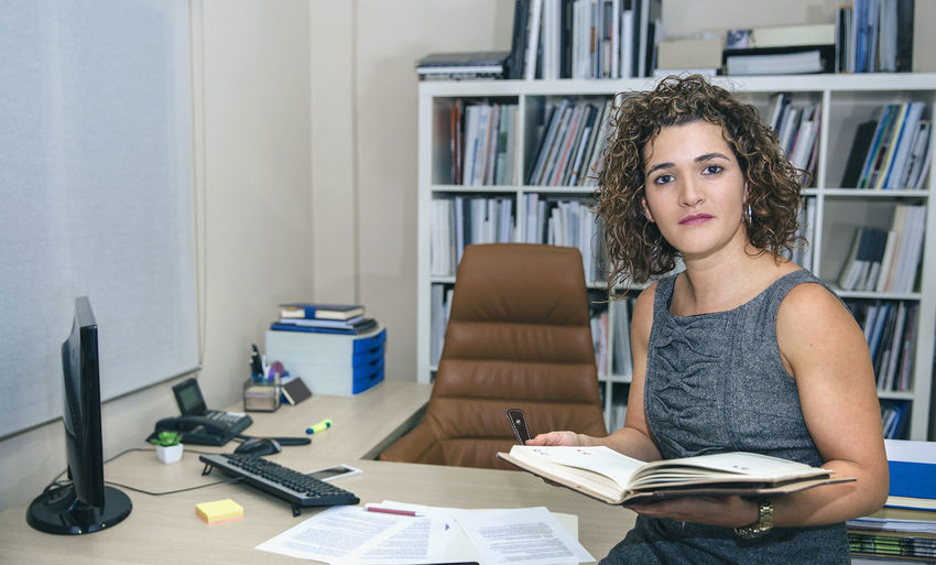 Young woman sitting on book
