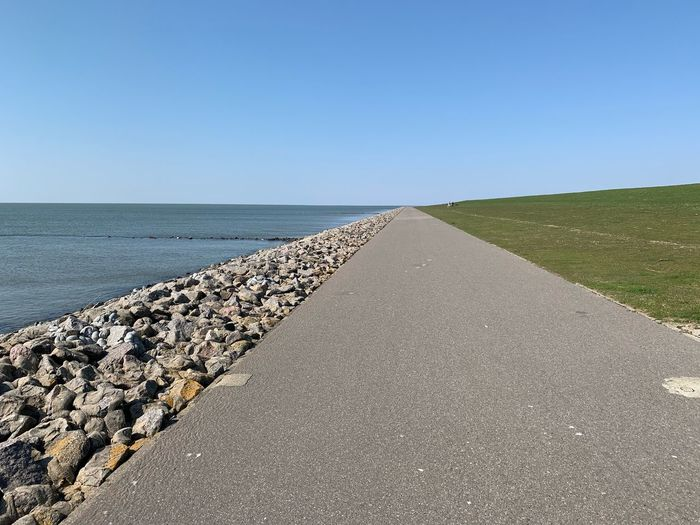 Road by sea against clear sky