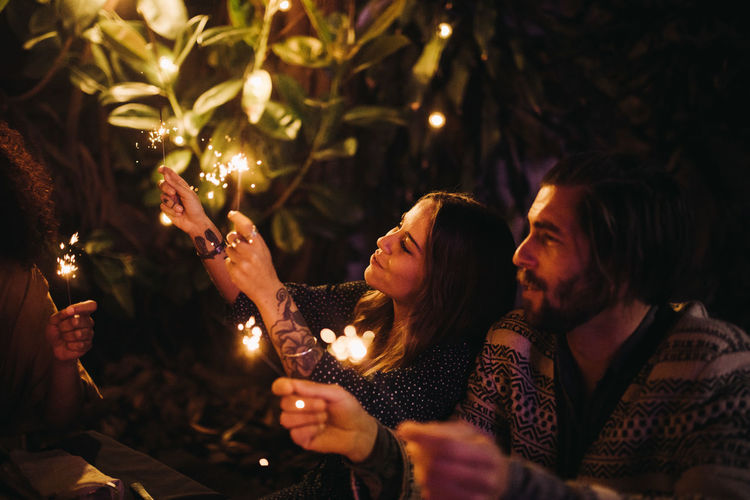 People on illuminated christmas tree