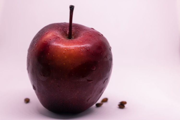 Close-up of wet apple against white background