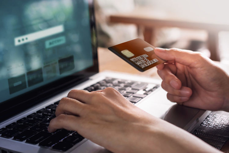 Cropped Image Of Hands Using Credit Card And Laptop