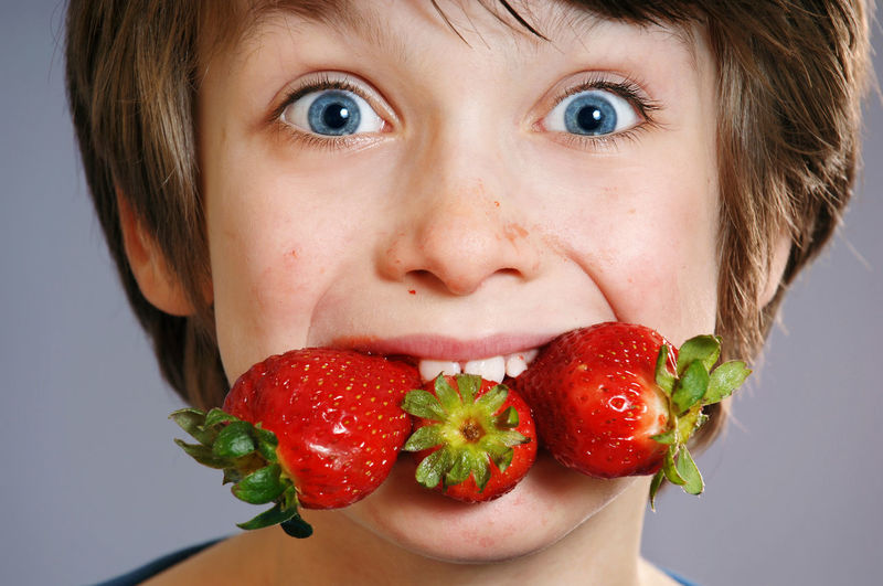 Close-up of boy with strawberries