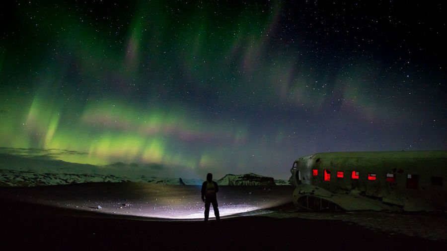 Silhouette Man Looking At Aurora Borealis While Standing By Abandoned Airplane