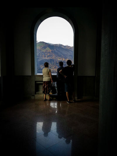 A family in a Portuguese sanctuary looking at the burned forest ahead. Portugal has suffered really hard this year with wild fires, and this is just one of the many places affected. Gerês, S. Bento da Porta Aberta - 2017. Full Length Indoors  Silhouette Adult Togetherness Adults Only People Architecture Friendship Day Water Politics And Government Arch GêresPortugal Landscape Burned Wild Fire Fires Burned Tree Burned Landscape Family Sad Sadness Religious Place EyeEm Best Shots