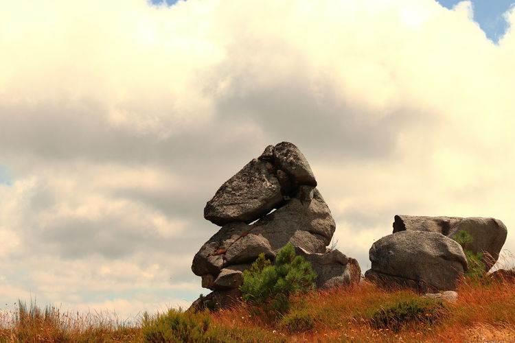 Stack of rocks on field against sky