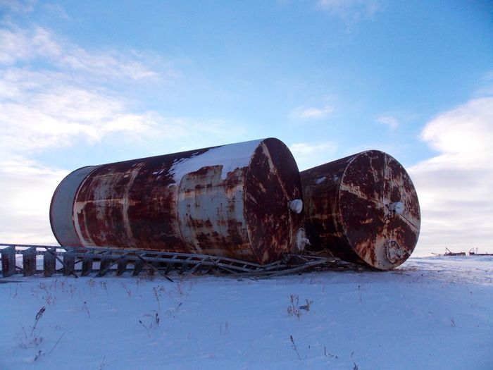 Abandoned large rust containers on snowed landscape