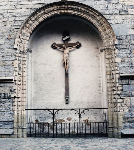 Jesus christ statue over cross against wall