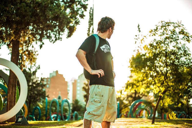 Man standing in park against sky