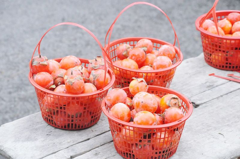 Bucket full of persimmons on table