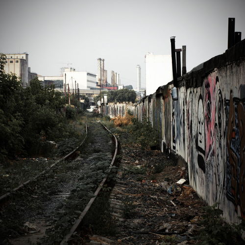 Empty railroad tracks in city against clear sky