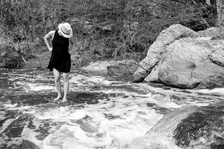 Full length of woman standing in flowing stream