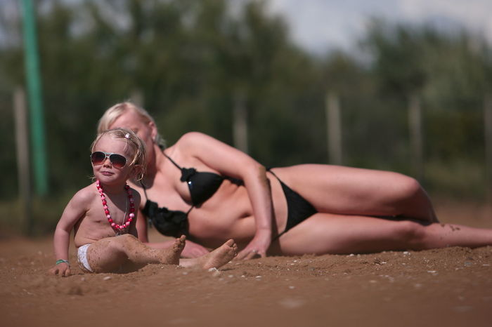 sunbath , Mother & Daughter 3 Years Abyssinian  Baby In Pink Corals, Pearls, And To Big Sunglasses Black Swimsuit Blonde Girl Fun Funny Hairs Mother & Daughter Small Smile Sunbath Sunbathing Venetian Sand