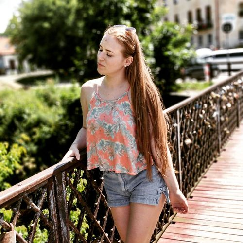 Young Woman With Eyes Closed Standing On Footbridge In City