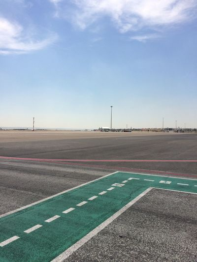 Empty runway against blue sky at airport
