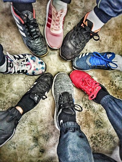 """the team"" Low Section Men Standing Human Leg Togetherness Shoe High Angle View Canvas Shoe Close-up Footwear Human Feet Feet Stone Tile Pair Human Foot Things That Go Together Personal Perspective Human Flat Shoe Shoelace Flip-flop Ground"