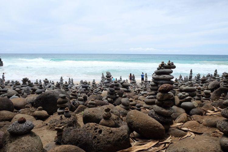 Pebble cairns at beach against cloudy sky