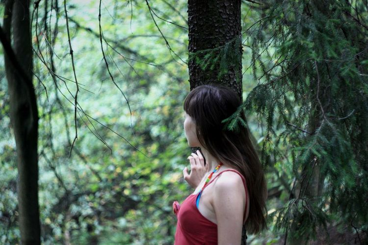 Side view of young woman standing by tree in forest