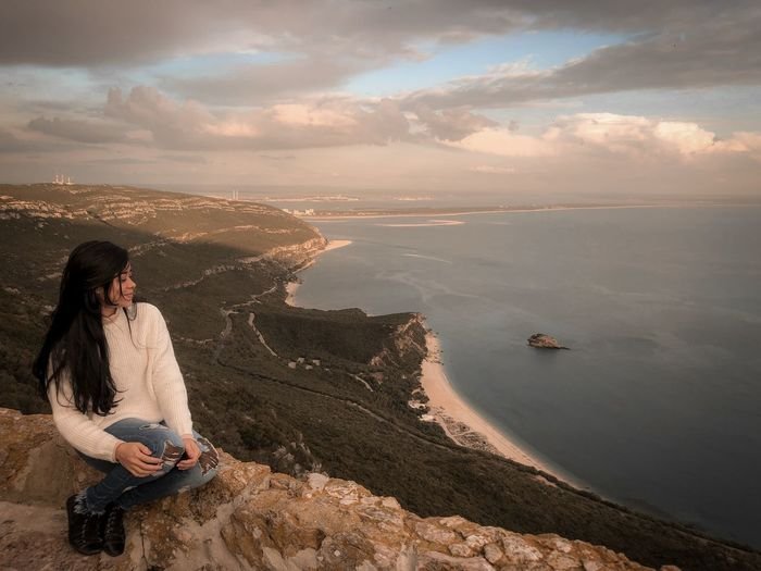 Woman sitting on cliff against sea during sunset