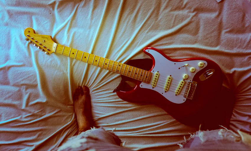Low section of person with guitar on bed