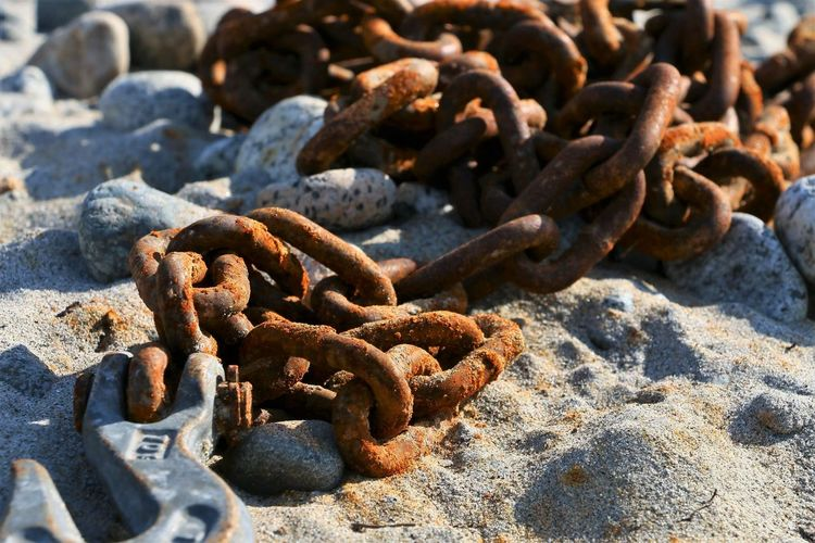 Rusty Chain Metal Close-up Day Solid No People Nature Sunlight Land Strength Rock Focus On Foreground Rock - Object Beach Outdoors Connection Run-down Still Life High Angle View Deterioration Iron