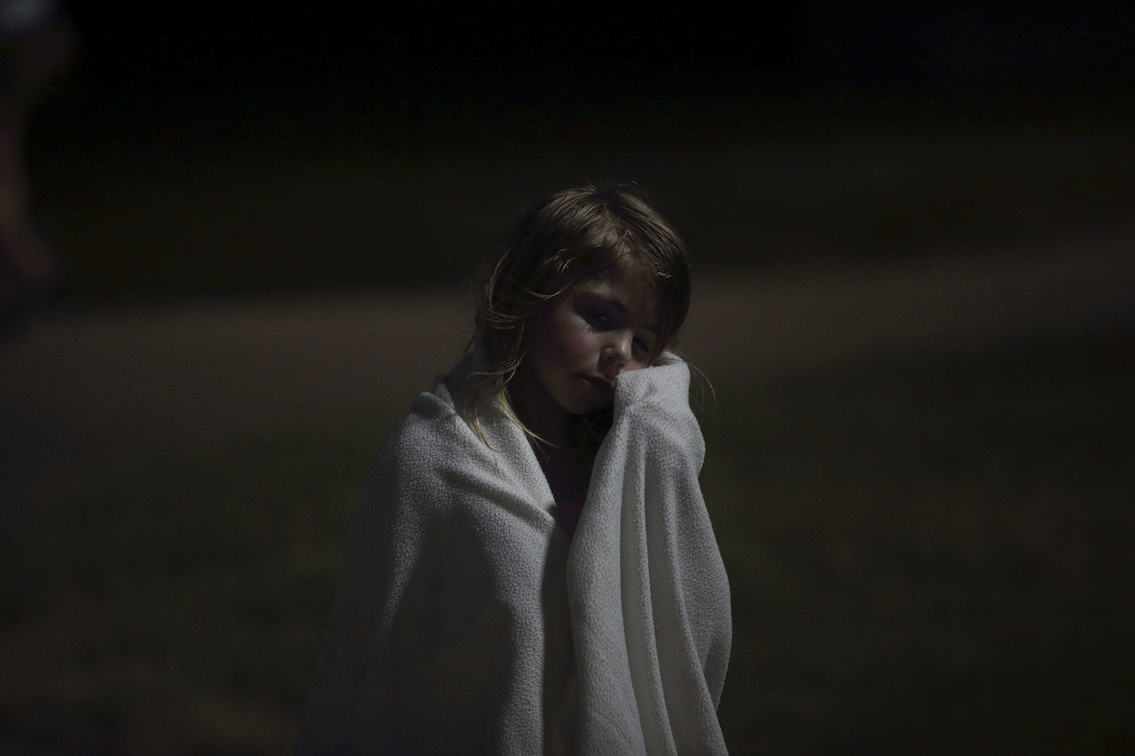 Close-up of girl wrapped in a towel at night