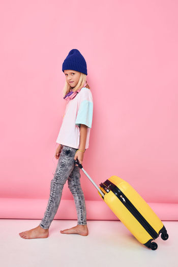 Full length of cute girl standing against pink background