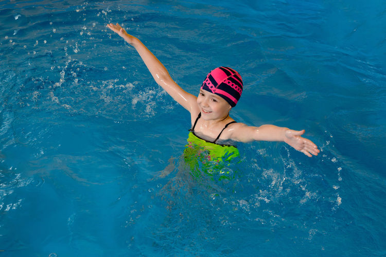 High angle view of girl with arms outstretched swimming in pool