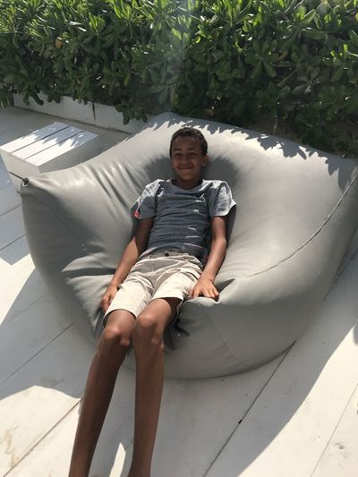Portrait Of Smiling Boy Relaxing On Bean Bag
