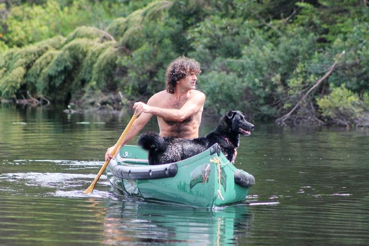 Side View Of A Man With Dog On Lake