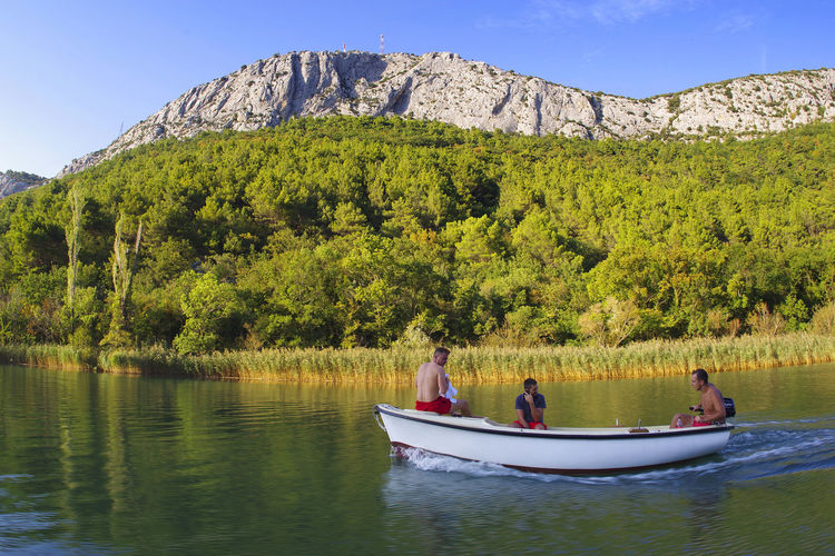 People in boat on mountain against sky