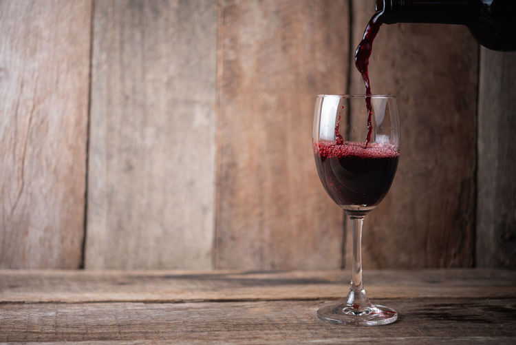 glass of wine on wood background Alcohol Alcoholic  Background Beverage Booze Bottle Cabernet Celebration Cellar Copy Cork Corkscrew Crystal Drink Elégance Fermentation Festive Fragrant Glass Gourmet Grape Harvest Healthy Liquid Merlot Natural Object Organic Party Pour Pouring Red Refreshment Romantic Scented Seasonal Space Table Taste Text Vine Vineyard Wine Wineglass Winery Winetasting Wood Wooden