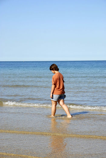Young girl walking on the beach Beach Child Children Only Clear Sky Day Full Length Horizon Over Water Nature One Person Outdoors Pen People Sea Sky Summer Thoughtful Vacations Walking Alone... Water