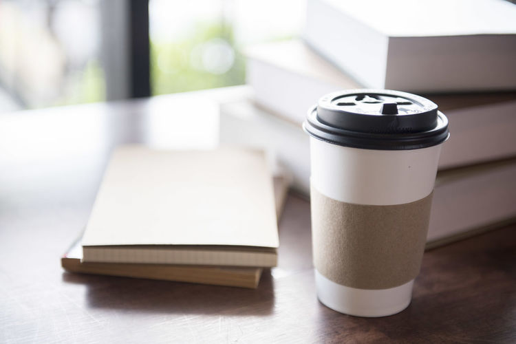 Close-Up Of Disposable Cup By Books On Table
