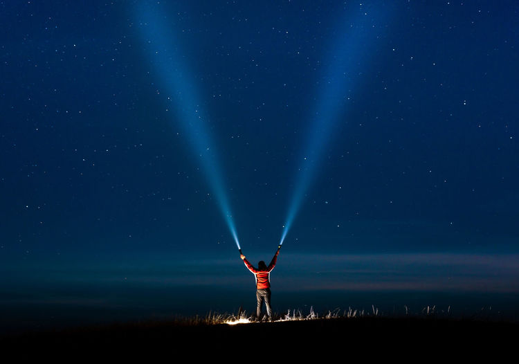Low angle view of person standing on field against sky at night