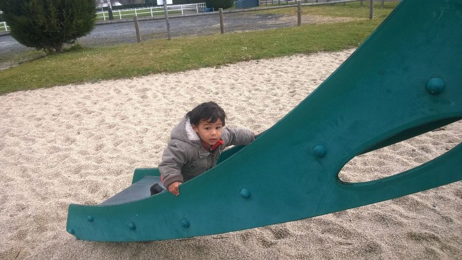 High Angle Portrait Of Boy Playing On Slide In Playground