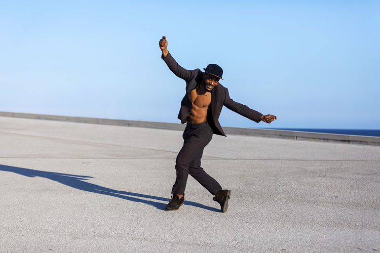 Front view of a black bearded man holding a hat while dancing and enjoying against blue sky in a sunny day Full Length One Person Sky Real People Day Leisure Activity Lifestyles Nature Sunlight Men Shadow Clear Sky Sea Arms Outstretched Human Arm Young Adult Young Men Casual Clothing Sunny Outdoors Horizon Over Water African American Black Man Dancing Muscular Build Suit Daylight Blue Sky Copy Space Males  Man Bearded Elegant Attractive Wellbeing