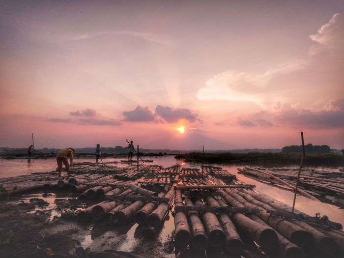 People On Bamboo Rafts Over Lake Against Sky During Sunset