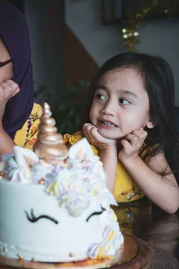 Cute girl looking at sister while sitting with birthday cake on table