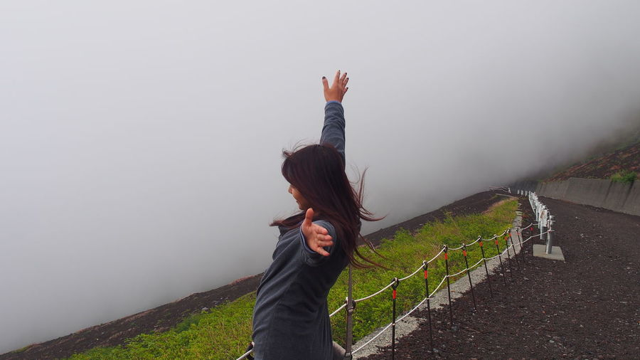 Side view of young woman with arms outstretched standing on mountain during foggy weather