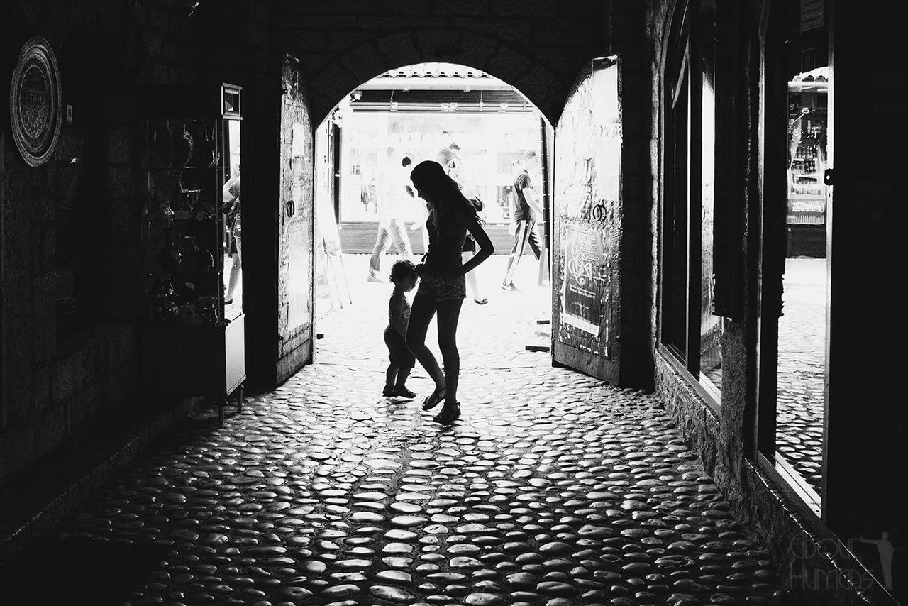 Silhouette people walking on cobblestone street