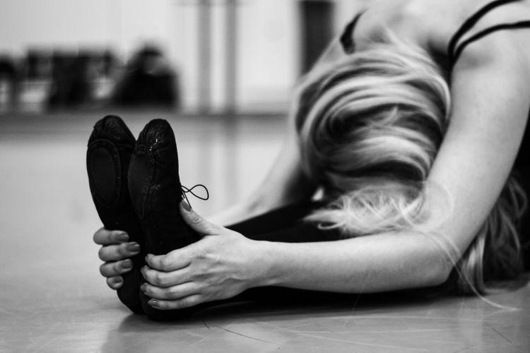 Ballet dancer stretching on floor