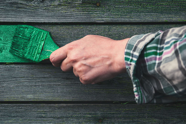 Female hand paints the weathered wooden wall of an old house with green paint, home redecoration
